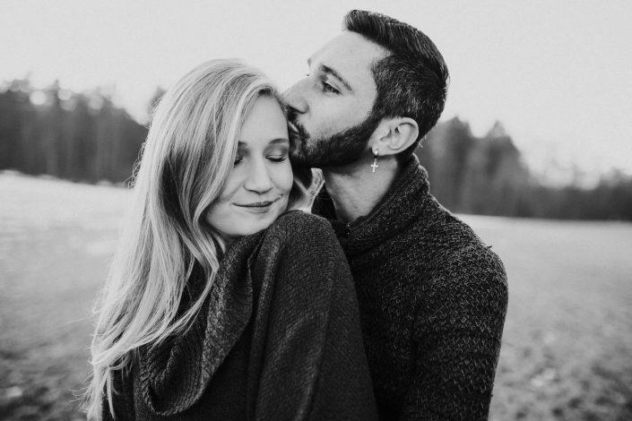 Portrait eines Paares, er küsst sie an der Schläfe