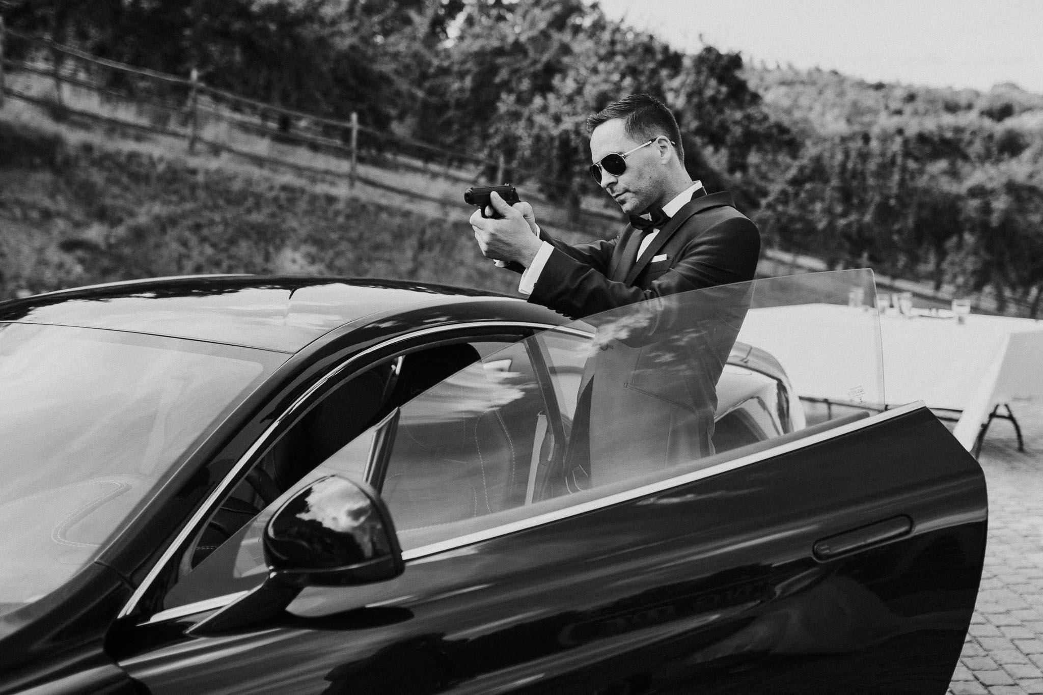 Oliver posiert als James Bond mit Waffe am Auto