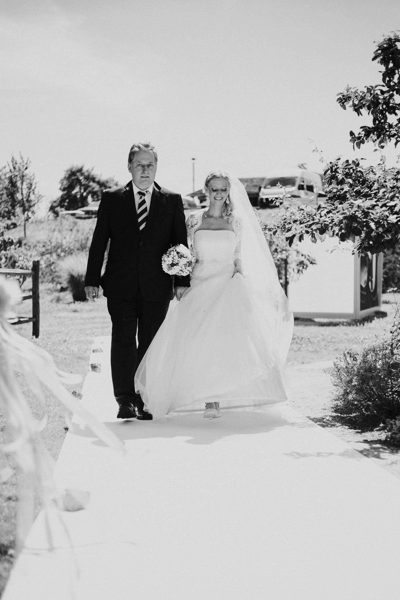 Braut wird von Vater zu Trauung geführt