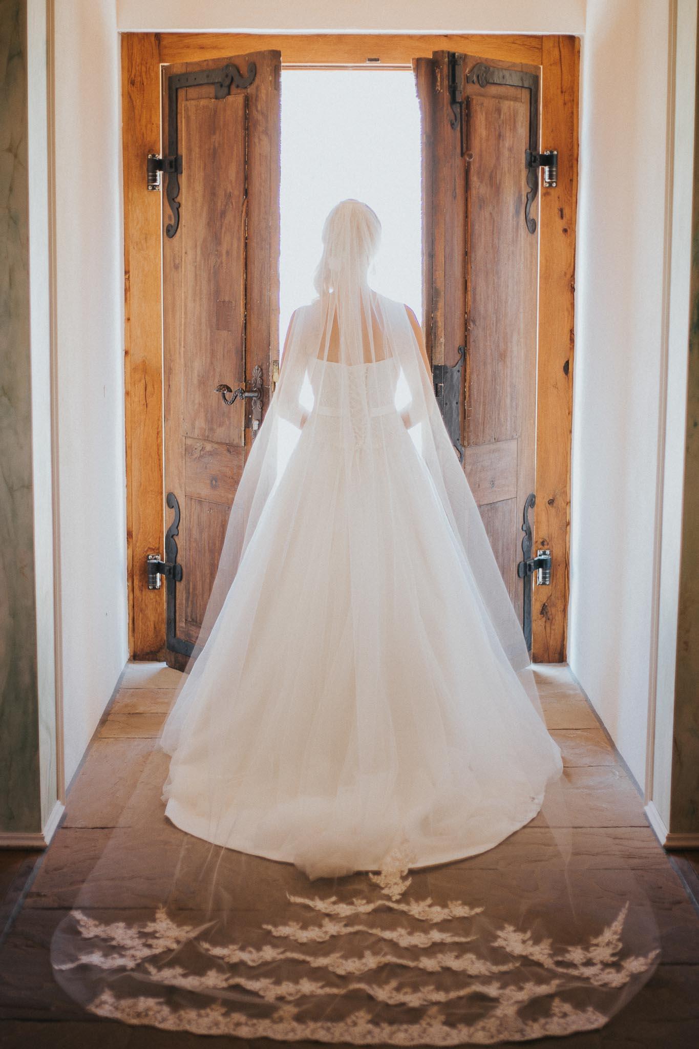 Die Braut von hinten an einer Tür