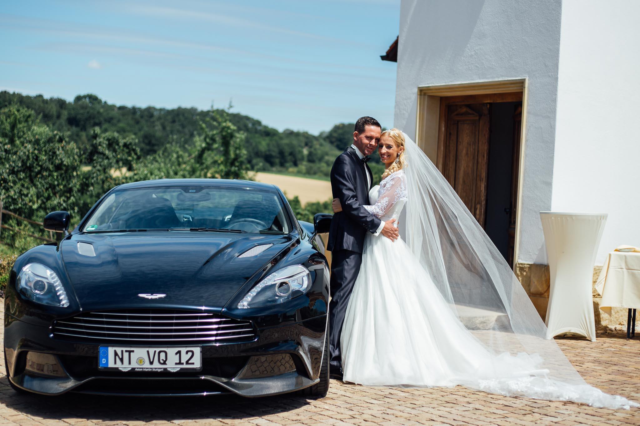 Braut posiert an ihrem James Bond Hochzeitsauto