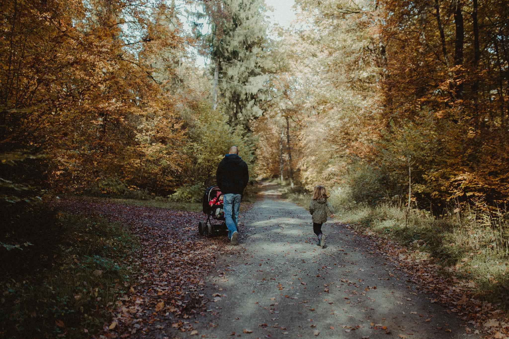 Familie, die durch den Herbstwald läuft