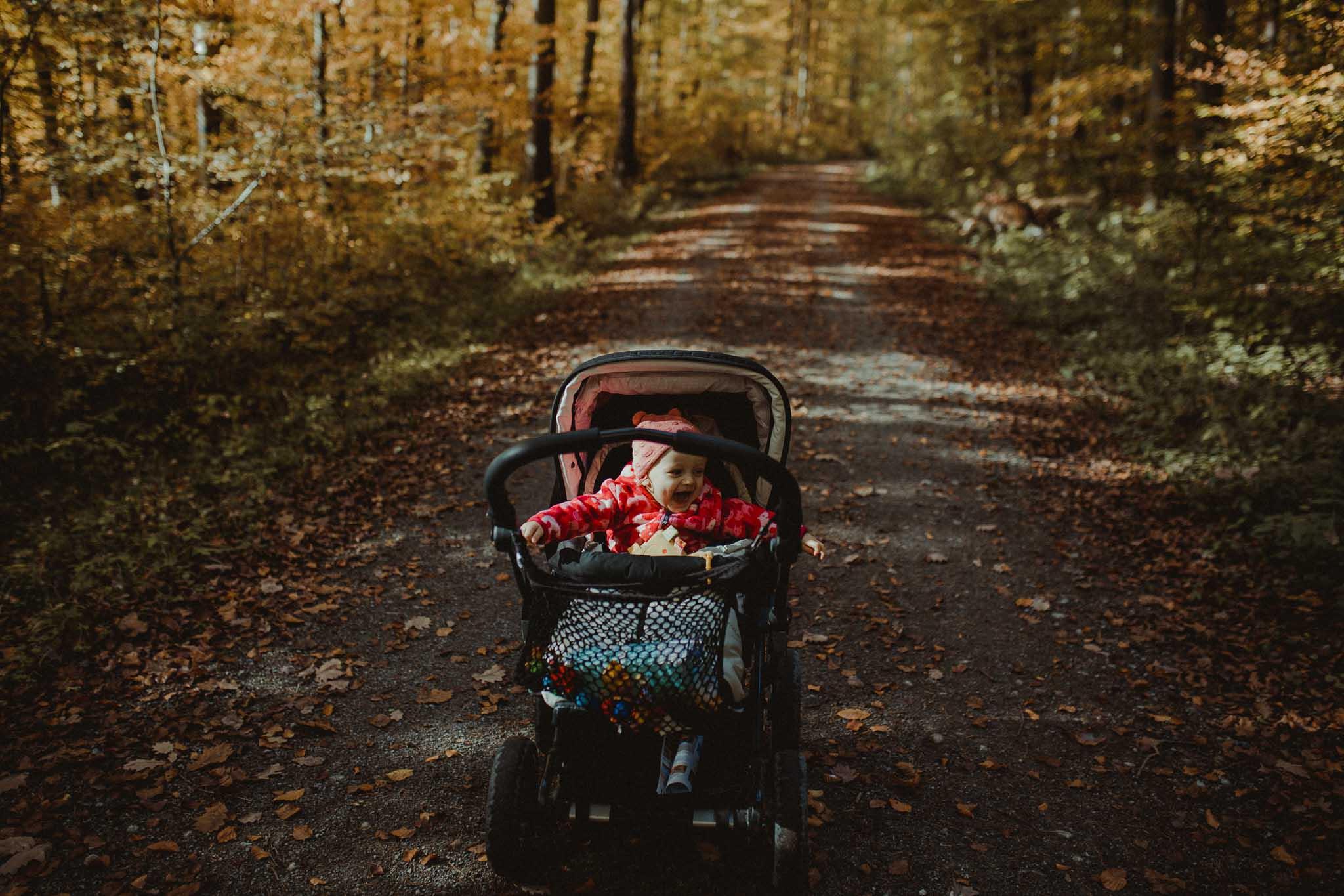 kleines Mädchen im Kinderwagen im Wald - Herbstspaziergang