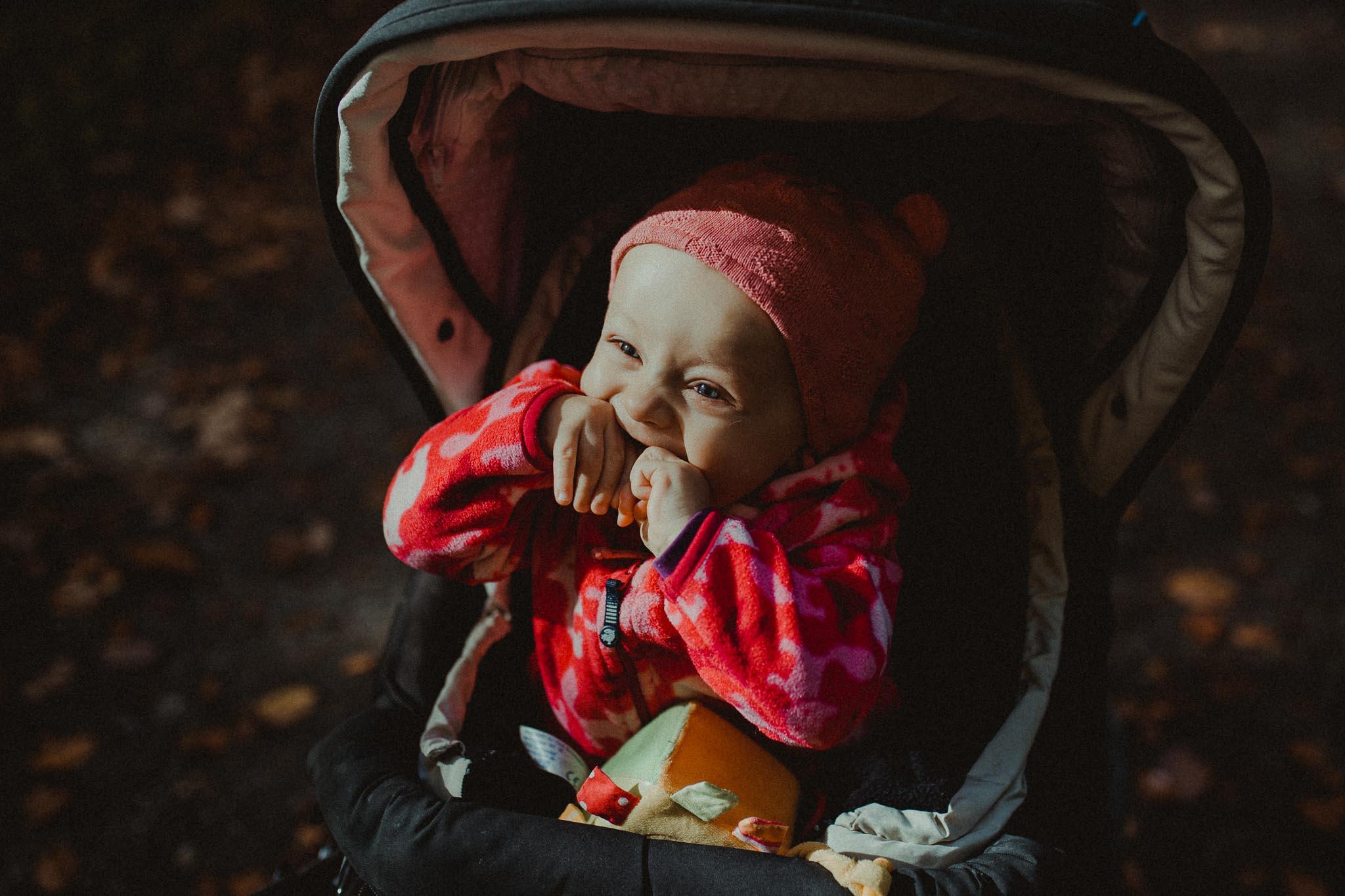 grinsendes kleines Mädchen im Kinderwagen im Wald