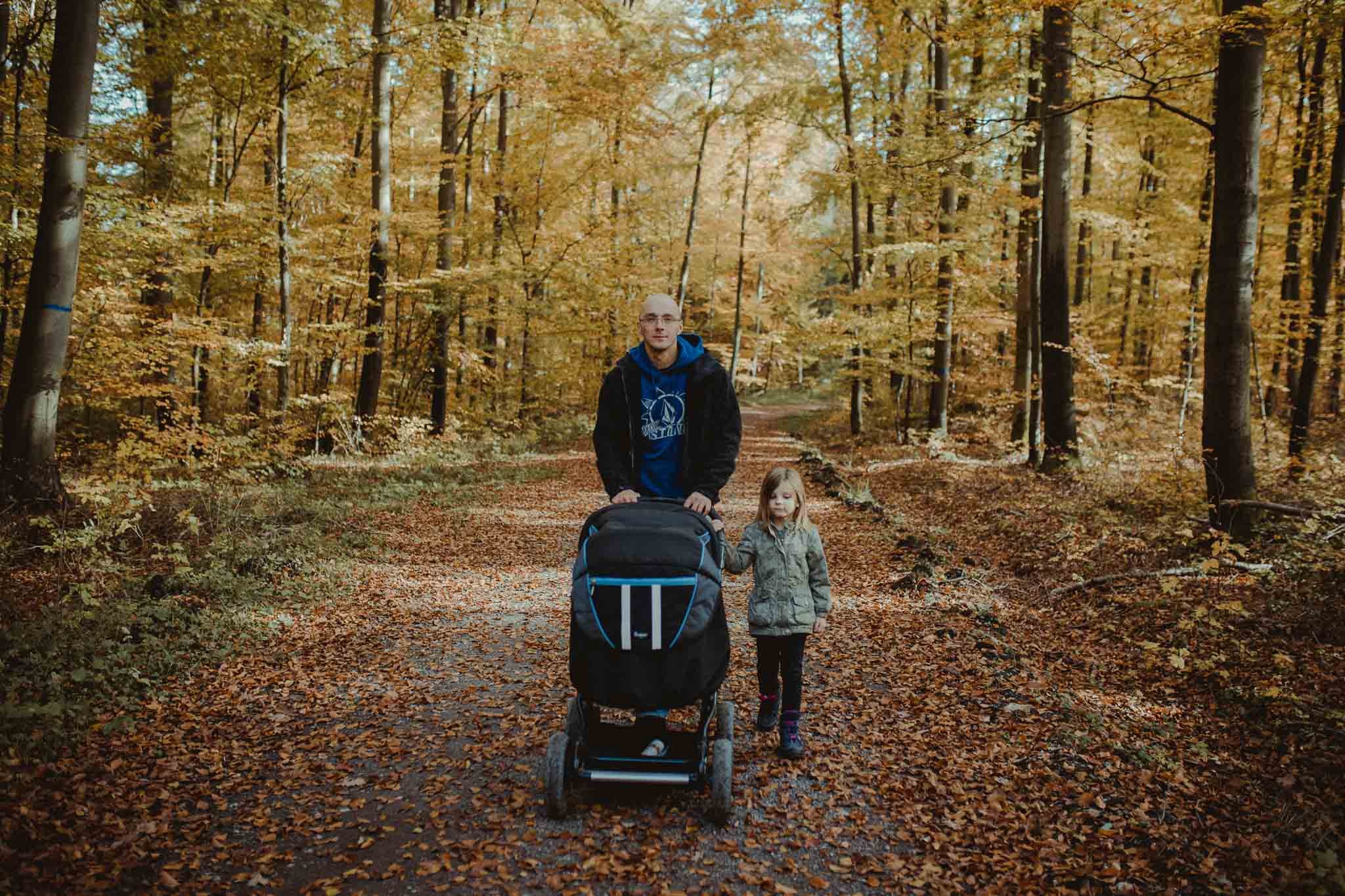 Vater mit Kinderwagen und Tochter im herbstlichen Wald beim Spaziergang
