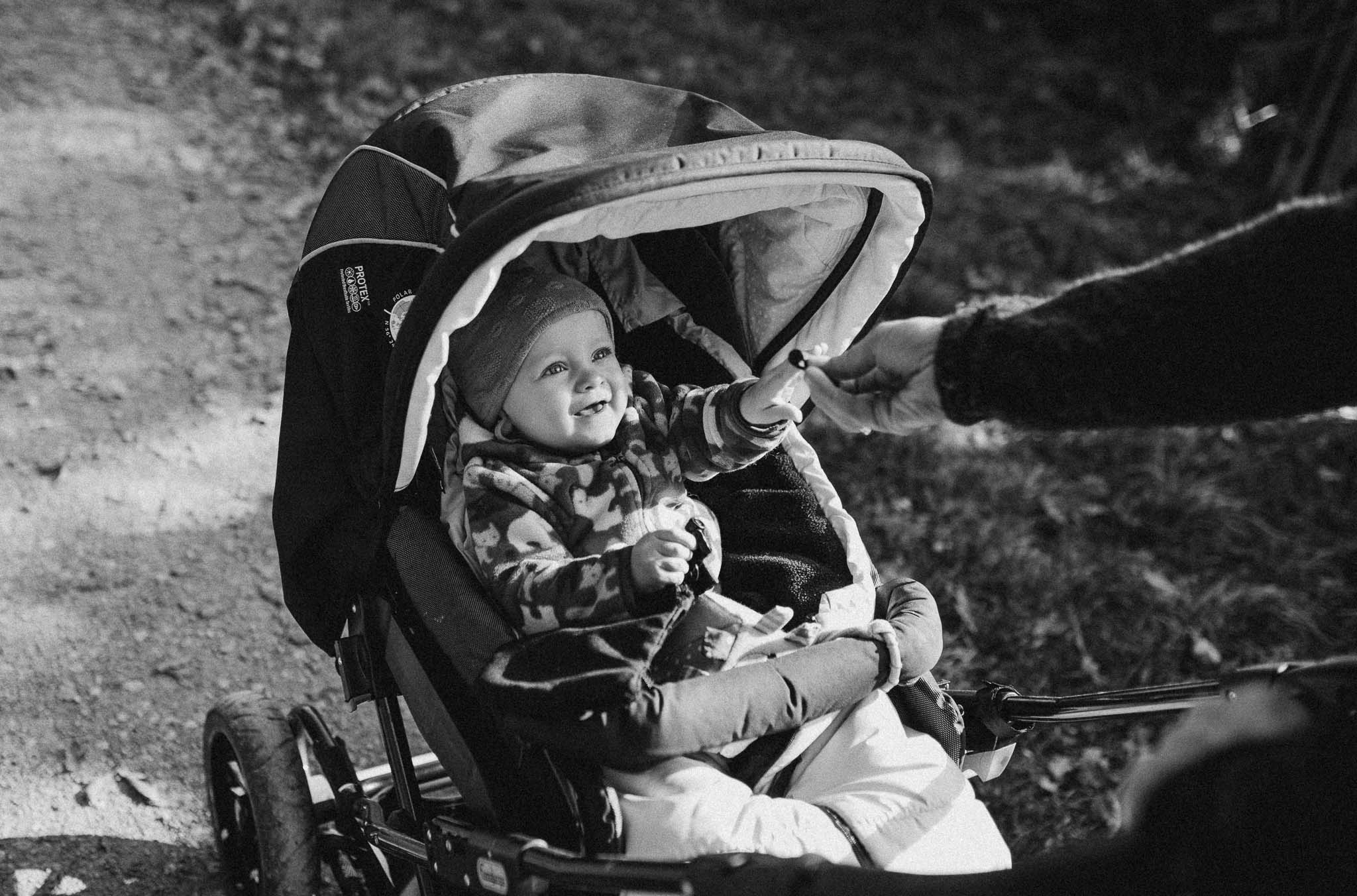 Kleines Mädchen im Kinderwagen beim Spaziergang mit der Familie
