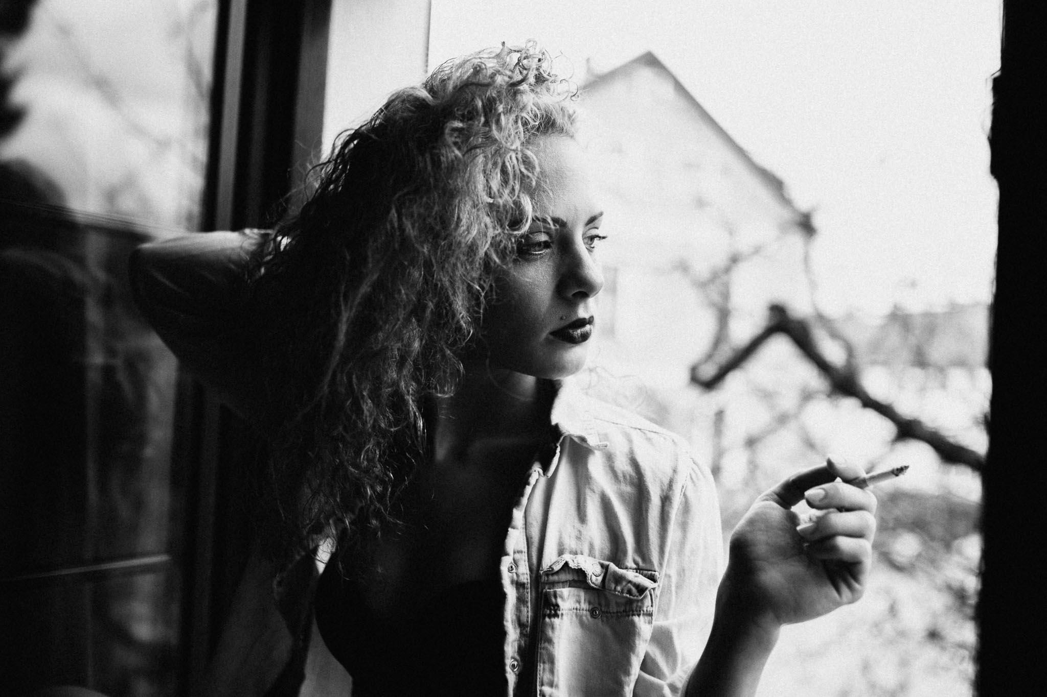 Model mit Zigarette am Fenster