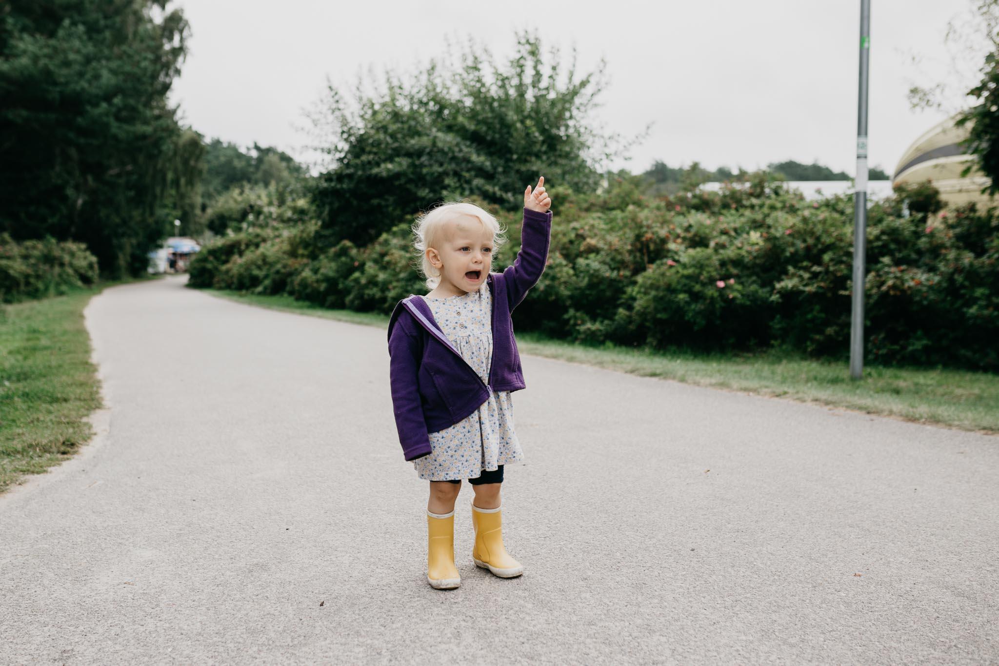 kleines Mädchen in gelben Gummistiefeln