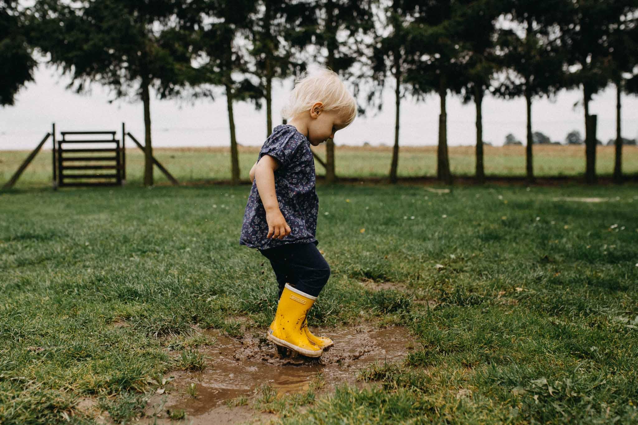 kleines Mädchen springt mit gelben Gummistiefeln in der Pfütze