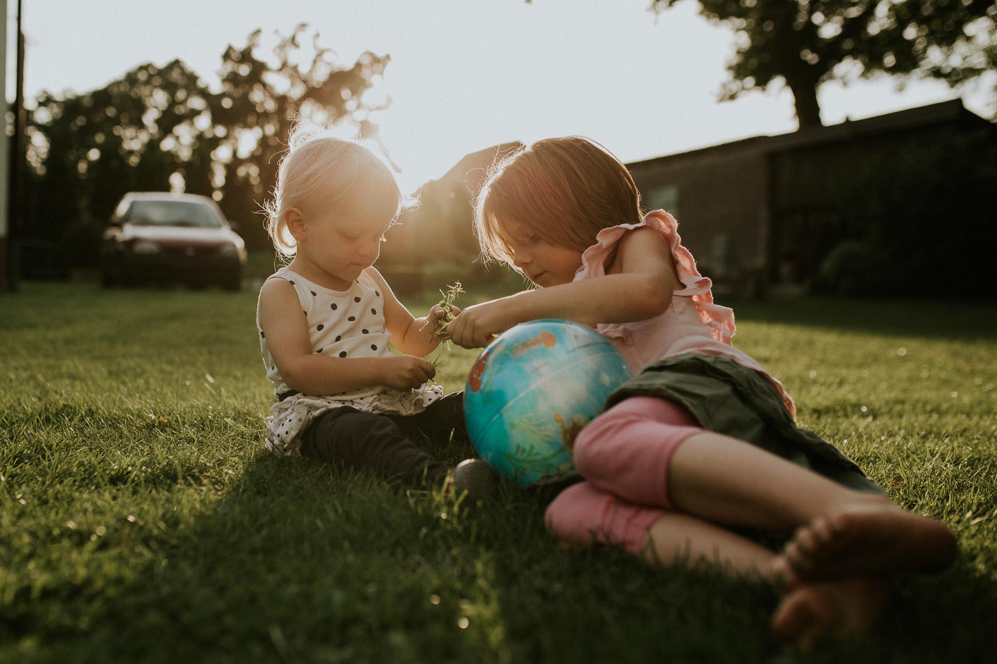 Zwei Mädchen sitzen auf der Wiese im Sonnenuntergang