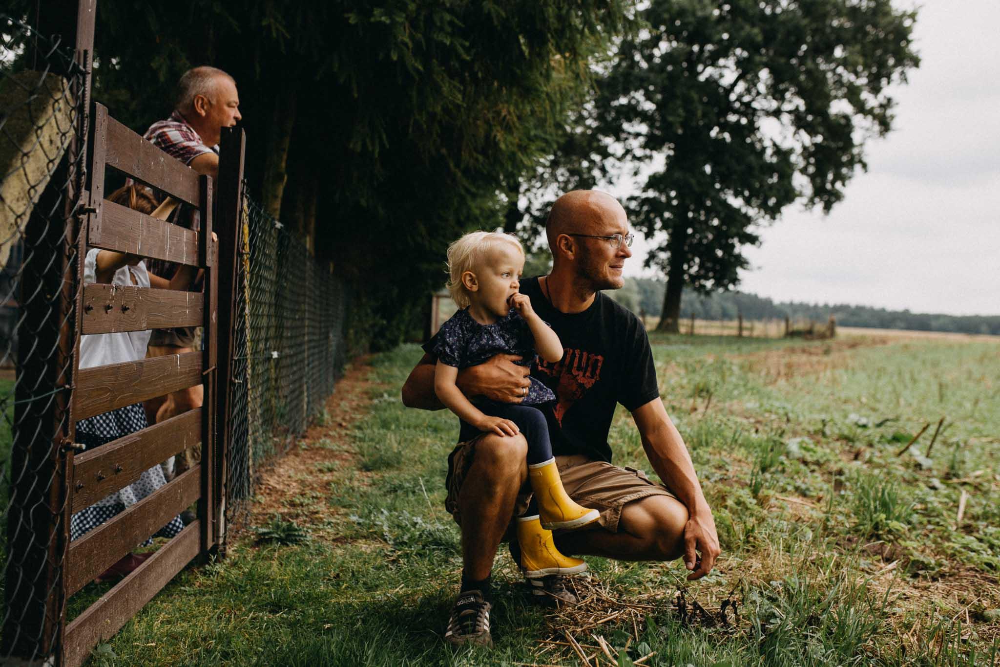 Familie schaut dem Trekker auf dem Feld zu