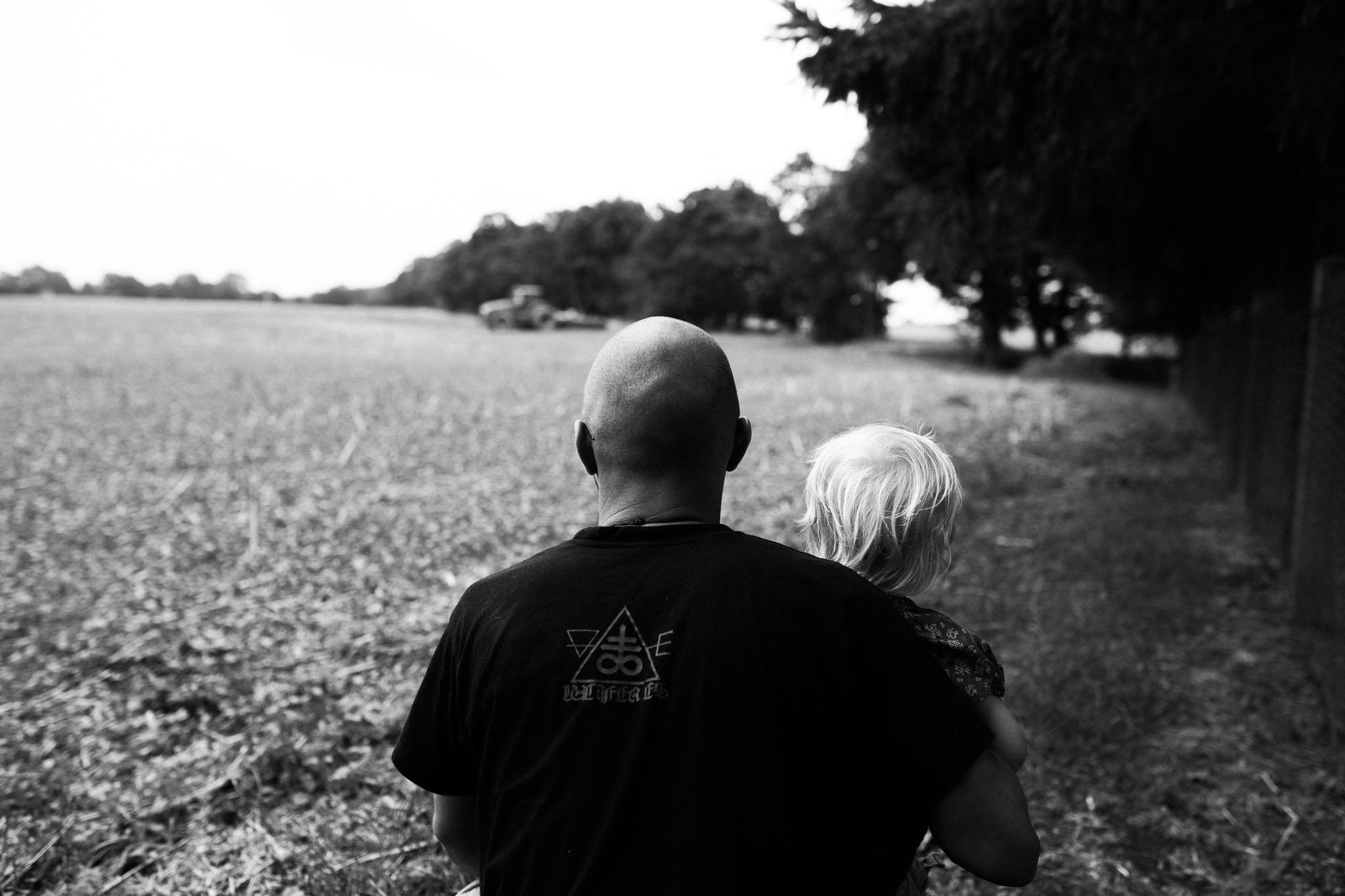 Vater und kleine Tochter schauen dem Trekker in der Ferne zu