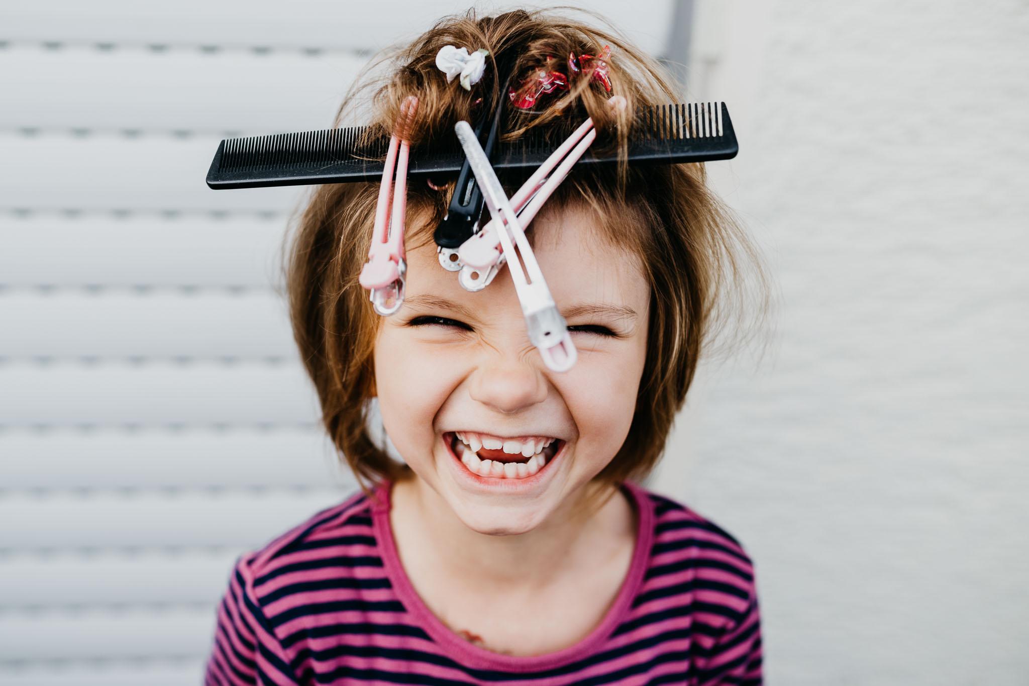Portrait eines Mädchens mit Kamm und Klammern auf dem Kopf