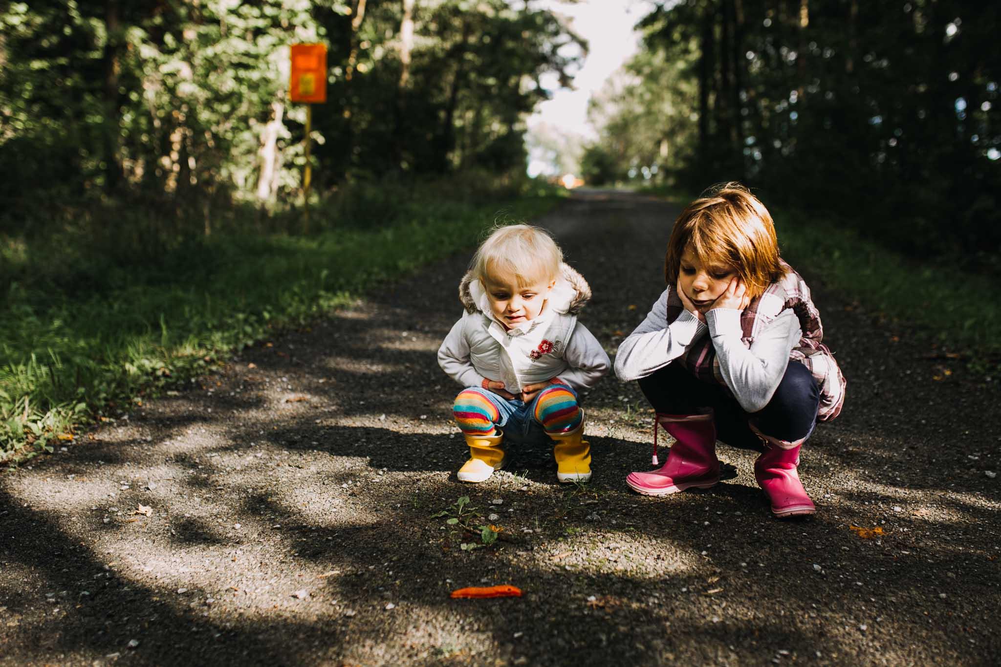 zwei Kinder beobachten eine Schnecke
