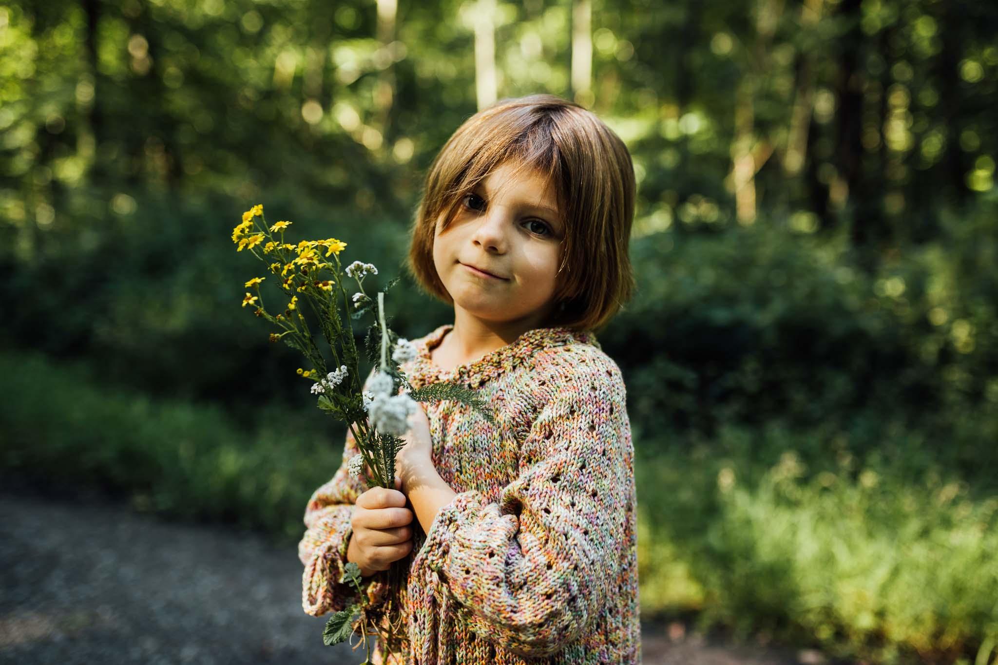 Mädchen mit Blumen in der Hand im Wald